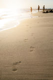 Footsteps on a sandy beach. Wave and sun. Holiday and travel concept. Summer vibes. Stock Photography