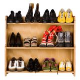 Footwear. Shoes, gym shoes, boots and other footwear stand on a rack stock photos