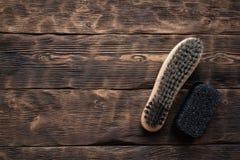 Footwear brush. Footwear brush on a brown wooden floor background royalty free stock image
