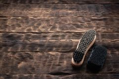 Footwear brush. Footwear brush on a brown wooden floor background stock photos
