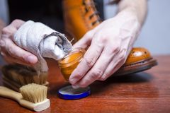 Footwear Care Ideas. Closeup of Mans Hands with Cleaning Tools P. Olishing Tan Derby Boots. Variety of Brushes Added. Horizontal Composition stock photography