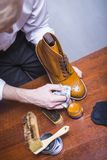 Footwear Cleaning Ideas. Professional Male Shoe Cleaner. Using Cloth and Brush For Tan Derby Boots. Working in Workshop. Vertical Image Royalty Free Stock Images