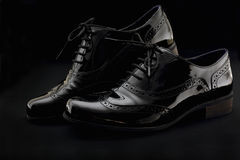 Footwear Concept. Horizontal Image. Pair of black female classic leather shoes on the black background. Stock Image