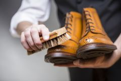Footwear concepts and ideas. Closeup of hands of man cleaning pr Royalty Free Stock Photo