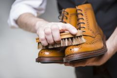 Hands of Man Cleaning Premium Derby Boots With Brush Royalty Free Stock Photography