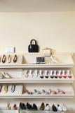 Footwear on display rack in shoe store Royalty Free Stock Photos