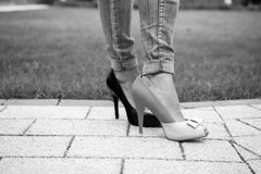 Footwear fashion, style. Legs in shoes and jeans on green grass background. Choice, choosing concept. High heels of different leather color on female feet stock photos