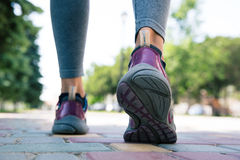 Footwear on female feet running on road. Outdoors royalty free stock images