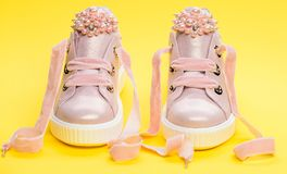 Footwear for girls or women decorated with pearl beads. Pair of pale pink female sneakers with velvet ribbons. Childrens. Shoes concept. Cute shoes on yellow stock image