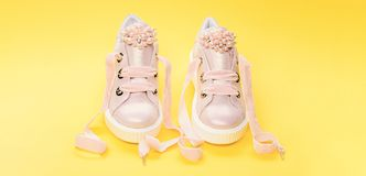 Footwear for girls or women decorated with pearl beads. Pair of pale pink female sneakers with velvet ribbons. Cute. Shoes on yellow background. Comfortable royalty free stock images