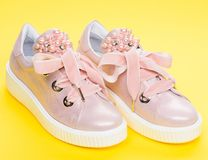 Footwear for girls or women decorated with pearl beads. Pair of pale pink female sneakers with velvet ribbons. Cute. Shoes on yellow background. Glamorous stock photography
