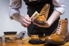 Footwear Ideas and Concepts. Extreme Close Up of Mans Hands Cleaning Luxury Calf Leather Brogues with Special Accessories, Shoe W stock image