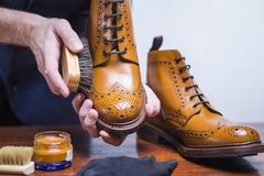 Footwear Ideas. Hands of Professional male Shoes Cleaner with Brush. Footwear Ideas. Hands of Professional male Shoes Cleaner with Cleaning Brush For Tan Derby Royalty Free Stock Image