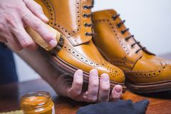Footwear Ideas. Hands of Professional male Shoes Cleaner. With Cleaning Brush For Tan Derby Boots. Working in Blue Apron in Workshop. Horizontal Shot Stock Photos