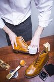 Footwear Ideas. Professional Male Shoes Cleaner Polishing Male Brogues. Footwear Ideas. Professional Male Shoes Cleaner Polishing Male Tan Brogue Derby Boots Royalty Free Stock Photography