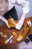Footwear Ideas. Professional Male Shoes Cleaner Polishing Male Tan Brogue. Derby Boots with Cream and Wax. Vertical Image Composition Stock Images