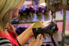 Footwear manufacture. Experienced worker sewing leather shoes in a production line royalty free stock photography