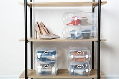 Footwear and plastic boxes on shelves near wall. Shoe storage organization stock images