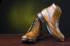 Footwear and shoes concepts. Pair of premium tanned brogue derb. Y Boots Shoot Against Dark Background.Horizontal Image Composition stock image