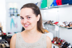 Footwear shop brunette girl posing with different shoes. And smiling Stock Photography