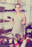 Footwear shop positive girl posing with different shoes. And smiling Stock Photos