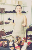 Footwear shop positive girl posing with different shoes. And smiling Royalty Free Stock Image