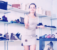 Footwear shop vigorous girl posing with different shoes. And smiling Stock Image