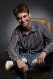 The fop. Portrait of the guy in a leather armchair against a dark background Stock Photography