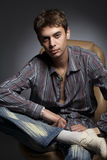 The fop. Portrait of the guy in a leather armchair against a dark background Royalty Free Stock Image