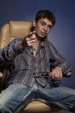 The fop. Portrait of the guy in a leather armchair against a dark background stock image