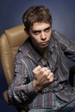 The fop. Portrait of the guy in a leather armchair against a dark background stock photos