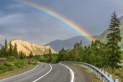 Forêt d'arc-en-ciel de montagne de route nuageuse Images stock