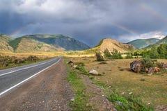 Forêt d'arc-en-ciel de montagne de route nuageuse Photographie stock