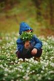 Forêt de petit garçon au printemps avec beaucoup de fleurs image stock
