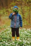 Forêt de petit garçon au printemps avec beaucoup de fleurs images stock