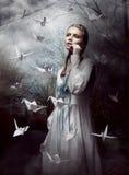 Nuit. La femme dans la forêt mystérieuse lançant le papier fait main tend le cou. Origami Photographie stock