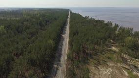 Forêt verte du côté gauche, lac bleu du côté droit, et longue route droite sur le milieu nature spectaculaire Vue sup?rieure banque de vidéos