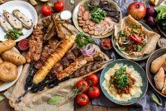 Fora conceito do alimento Bife assado apetitoso, salsichas e vegetais grelhados em uma tabela de piquenique de madeira foto de stock