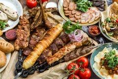 Fora conceito do alimento Bife assado apetitoso, salsichas e vegetais grelhados em uma tabela de piquenique de madeira imagem de stock royalty free