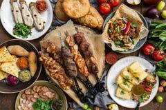 Fora conceito do alimento Bife assado apetitoso, salsichas e vegetais grelhados em uma tabela de piquenique de madeira imagens de stock royalty free