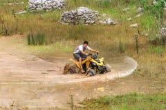 Fora da estrada na bicicleta do quadrilátero 4x4 através da poça de lama Foto de Stock
