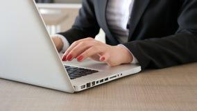 Fora de foco no foco da mulher de negócios entrega a datilografia rapidamente no laptop video estoque