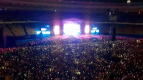 Fora do vídeo do foco da cena brilhantemente iluminada no concerto no estádio grande A multidão é de dança e de ondulação com tel vídeos de arquivo