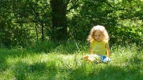 Fora retrato da menina bonita com o cabelo encaracolado curto louro que senta-se na grama verde, na colheita e no jogo video estoque