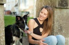 Fora retrato da menina consideravelmente atrativa que passa o tempo com seu cão preto durante o dia de verão Fotografia de Stock Royalty Free