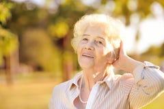 Fora retrato da mulher superior de sorriso bonita com cabelo branco encaracolado fotografia de stock royalty free