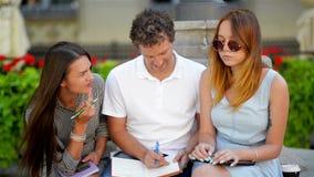 Fora retrato dos estudantes novos de sorriso engraçados que sentam-se no Brench no parque da cidade e que preparam-se para o exam video estoque