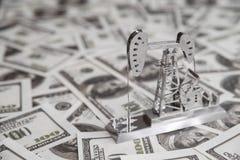 Forage de pétrole une pompe sur un fond du dollar avec des billets de banque d'argent Photos stock