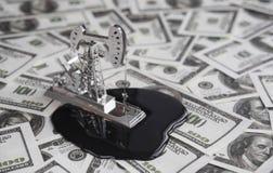 Forage de pétrole une pompe sur un fond du dollar avec des billets de banque d'argent Image libre de droits