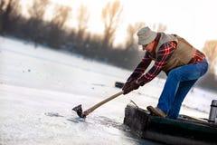 Forage de pêcheur pour la pêche d'hiver sur le lac congelé Image libre de droits